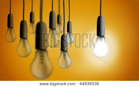 Light bulb lighting up against orange background