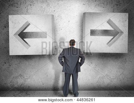 Businessman deciding which way to go on a grey wall