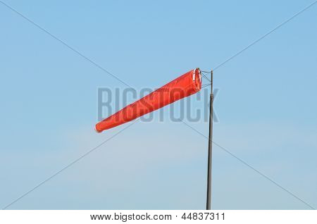 A bright orange windsock fully extended against a bright blue sky,