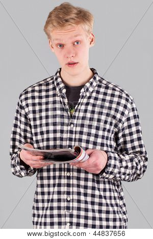 Portrait of young handsome guy holding a journal over grey background
