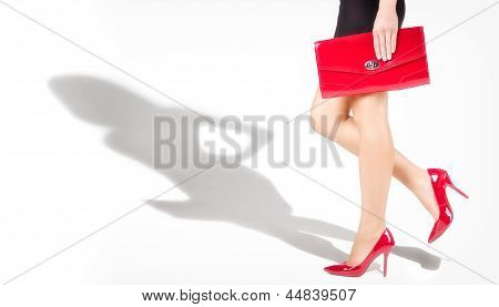 Beautiful slender female legs in red shoes, the shadow of the model