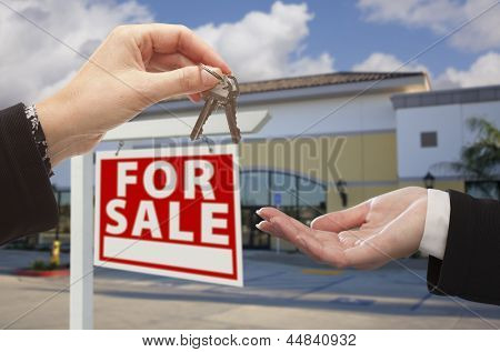 Real Estate Agent Handing Over the Keys in Front of Vacant Business Office and For Sale Sign.