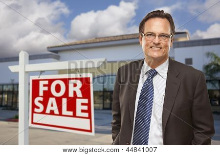 Handsome Businessman In Front of Vacant Office Building and For Sale Real Estate Sign.