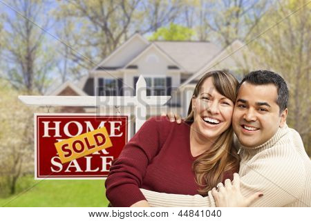 Happy Mixed Race Couple in Front of Sold Home For Sale Real Estate Sign and House.