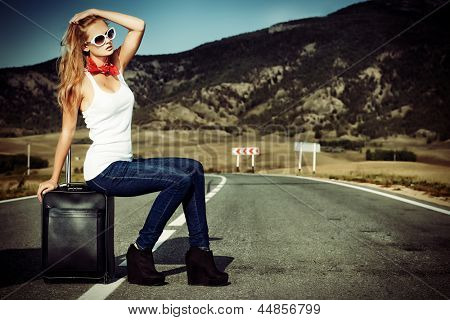 Attractive young woman hitchhiking along a road.