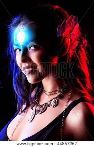 Portrait of a beautiful young woman with fantasy makeup. Black background.