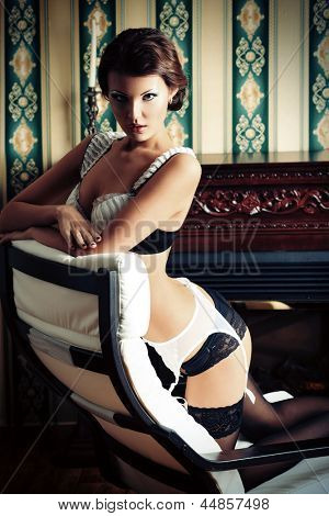 Seductive young woman in sexy lingerie posing in the vintage interior.