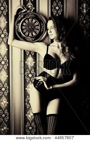 Seductive young woman in sexual lingerie posing over vintage background.