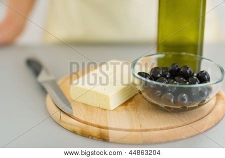 Closeup On Knife Cheese, Olives And Olive Oil On Cutting Board