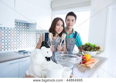 Young happy couples prepare vegetable salad in domestic kitchen