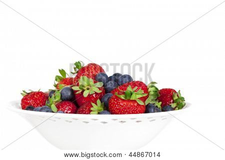 Strawberries and blueberries in bowl, isolated over white background.