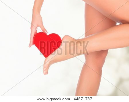 Female legs against a pastel background with blurred lights