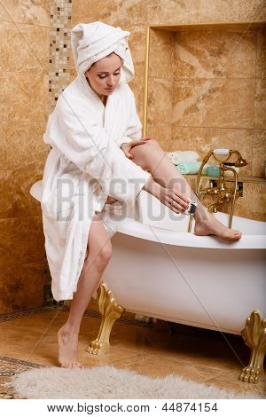Woman Shaving Her Legs In Bathroom.