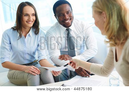 Young businesswoman asking her partners sign paper at meeting