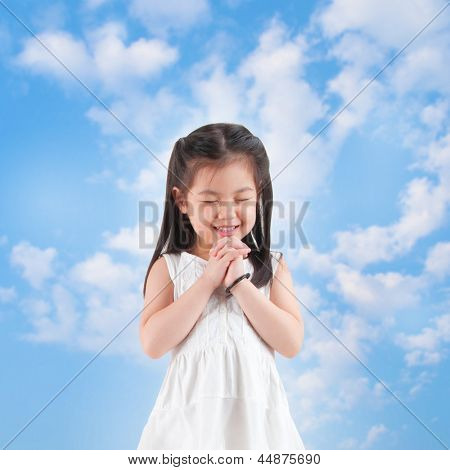 East Asian girl making a wish with smiling, blue sky as background