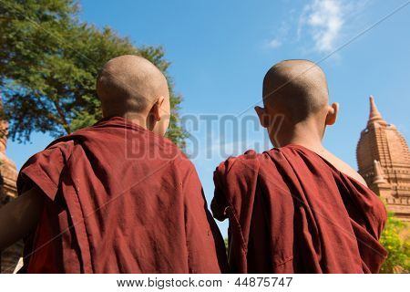 Rear view of two little monks standing under hot sun at Bagan, Myanmar