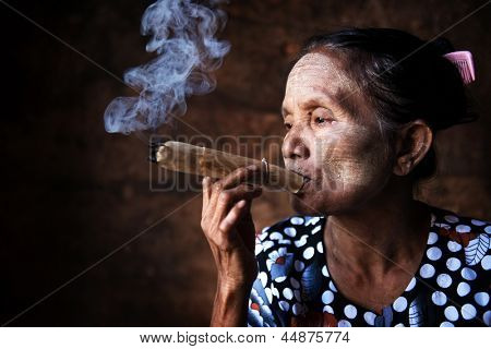 Old wrinkled Asian woman smoking traditional tobacco. Bagan, Myanmar.
