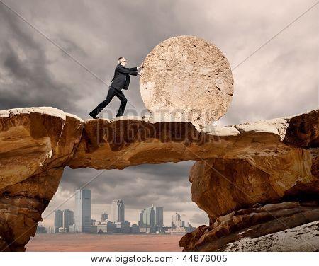 empresario empujando una rueda de piedra