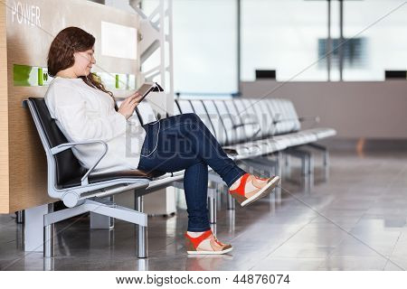 Young Caucasian Woman Spending Time In Airport Lounge