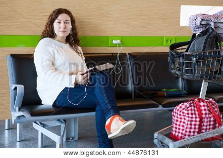 Serene Woman Charging Tablet Pc In Airport Lounge With Luggage Hand-cart