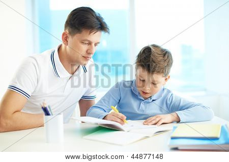 Photo of little boy drawing or writing in copybook with his father near by
