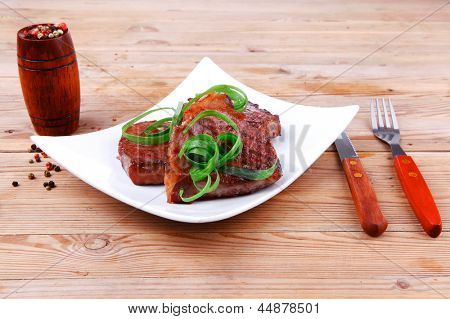 grilled meat beef steaks strips on white plate with pepper and cutlery over wood table