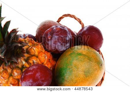 diet food - a lot of fresh raw tropical fruits include pineapple plum and mango in small basket isolated over white background