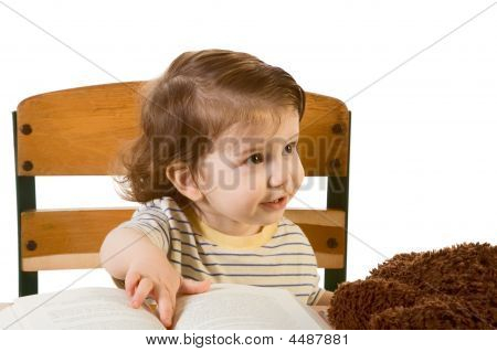Early Education Baby Boy With Book At School Desk