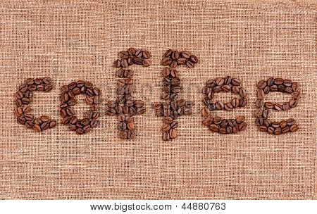 Word coffee made from coffee beans on burlap