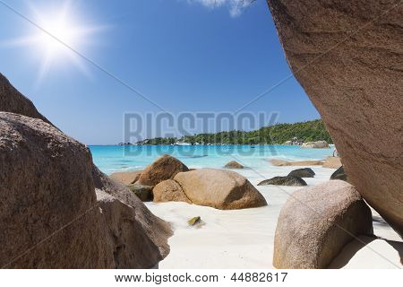 White Coral Beach Sand And Azure Indian Ocean. Sailing Yacht On Background.