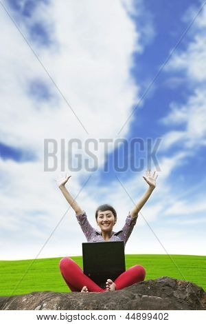 Asian Woman Using Laptop While Sitting In The Park