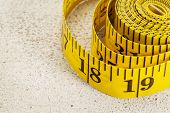 yellow inch tape measure on a rough white painted barn wood background