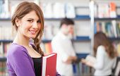 stock photo of exams  - Portrait of a beautiful student in a library - JPG