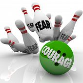 image of overcoming obstacles  - A bowling ball marked Courage strikes pins with the word Fear to symbolize bravery and courageous action to overcome obstacles you - JPG