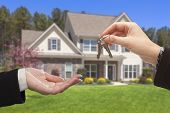 stock photo of yard sale  - Real Estate Agent Handing Over the House Keys in Front of a Beautiful New Home - JPG