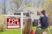 foto of yard sale  - Curious Family Facing For Sale Real Estate Sign and Beautiful New House - JPG