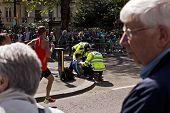 LONDON, UK - APRIL 21: Male runner on London Marathon receiving help from Police officers after suff