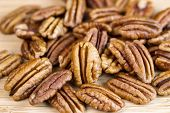 picture of pecan  - Horizontal photo of slightly roasted pecan nuts with focus of standing pecan in front of pile on natural wood - JPG