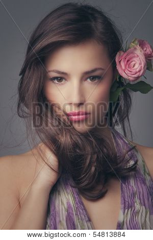beautiful young  woman portrait with roses in hair looking at camera studio shot