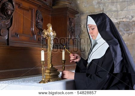 Medieval 17th century altar with a nun lighting the candles