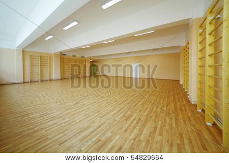 Empty school gymnasium with yellow floor and climbing near walls.