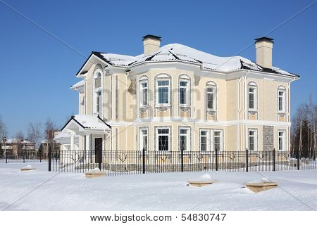 Two-storey light cottage with fence at frosty and sunny winter day.