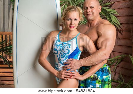 Muscular man and beautiful girl on a beach with a surfboard near the wooden house