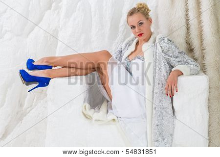 Beautiful girl in white dress and coat of Snow Maiden sitting with legs in snow chair
