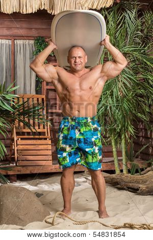 Muscular man on a sandy beach with a surfboard under the head