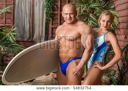 Muscular man in trunks and beautiful girl in swimsuit with a surfboard on a beach