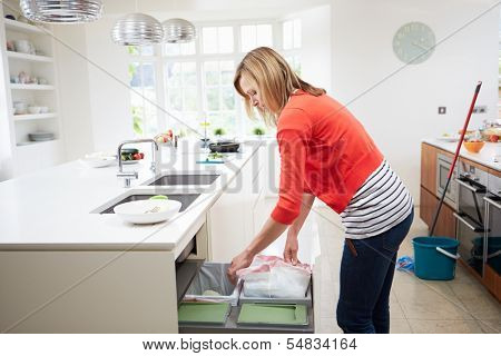 Woman Standing In Kitchen Emptying Waste Bin