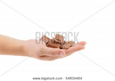 Hand holds tasty morsel of milk chocolate.