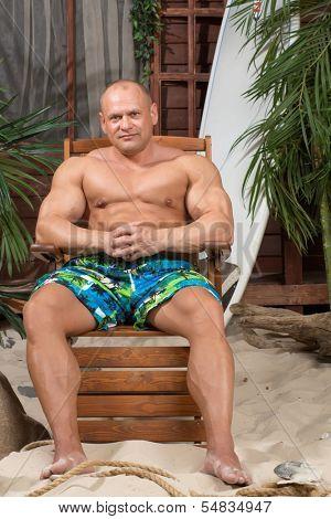 Muscular man on a sandy beach with a surfboard near the house