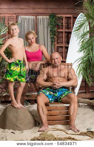 A modern family of three on a sandy beach with a surfboard near the house